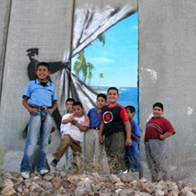 LA felicidad de niños palestinos viendo el hueco de libertad pintado en la pared que coloniza...