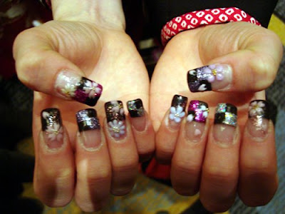 Elaborately painted and sculptured nails complete with flowery rhinestones