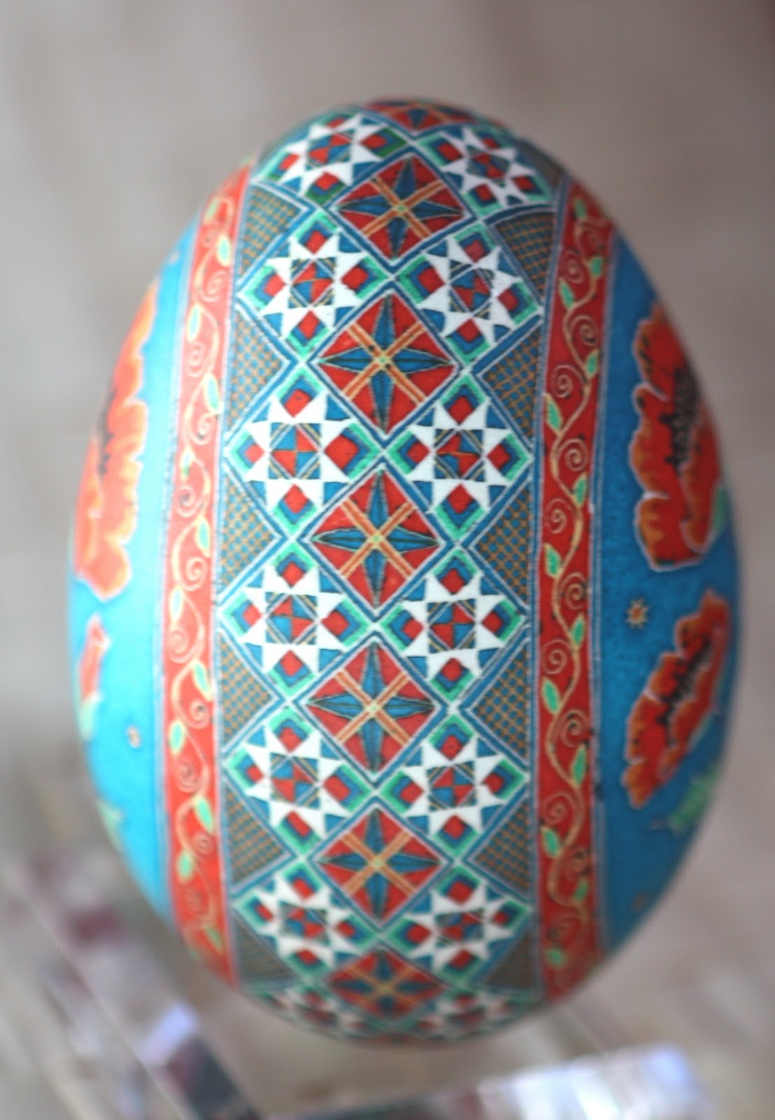 Traditional Red Poppy Goose Egg Pysanky on Turquoise Blue Background