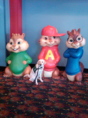 Poppy sitting with giant Alvin and the Chipmunks statues