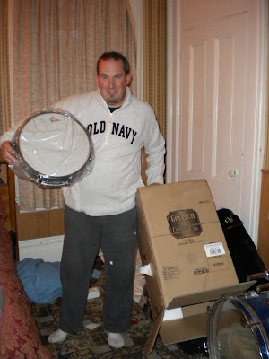 John with a huge grin, holding one of his new drums