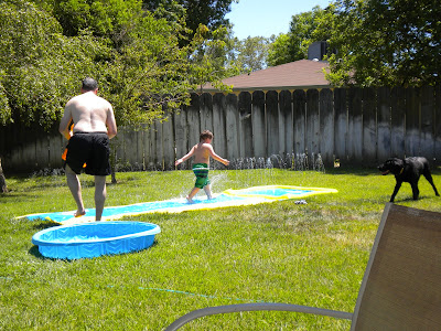 Brian walking down the slip-n-slide with John following him. Dagan standing back, looking on