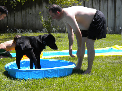Dagan standing in the pool with John next to him playing