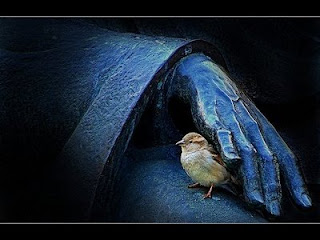 Foto passarinho sob mão de estátua