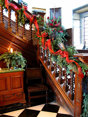 The entrance hall festooned with foliage swags and fresh flower arrangements