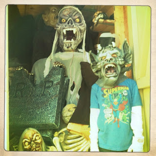 A child wearing a Superman t-shirt and monster mask standing in front of a shed filled with Halloween decorations