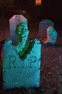 Zombie peeking up from behind a tombstone in a graveyard