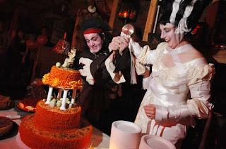 Photo of a couple cutting their wedding cake while dressed as a pirate and the Bride of Frankenstein