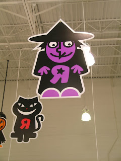 Photo of a witch graphic hanging in a Toys R Us Store at Halloween