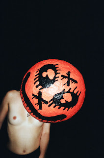 Topless model wearing a paper-mache pumpkin on her head