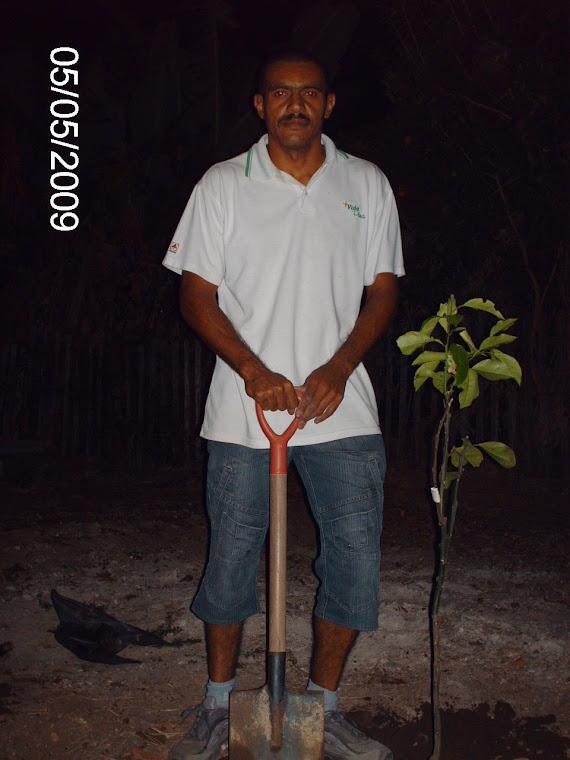 O funcionário Edilson da Escola Ruy Coelho e a muda laranja-do-céu plantada em sua casa.