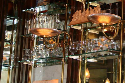 glasses and mirrors behind a bar