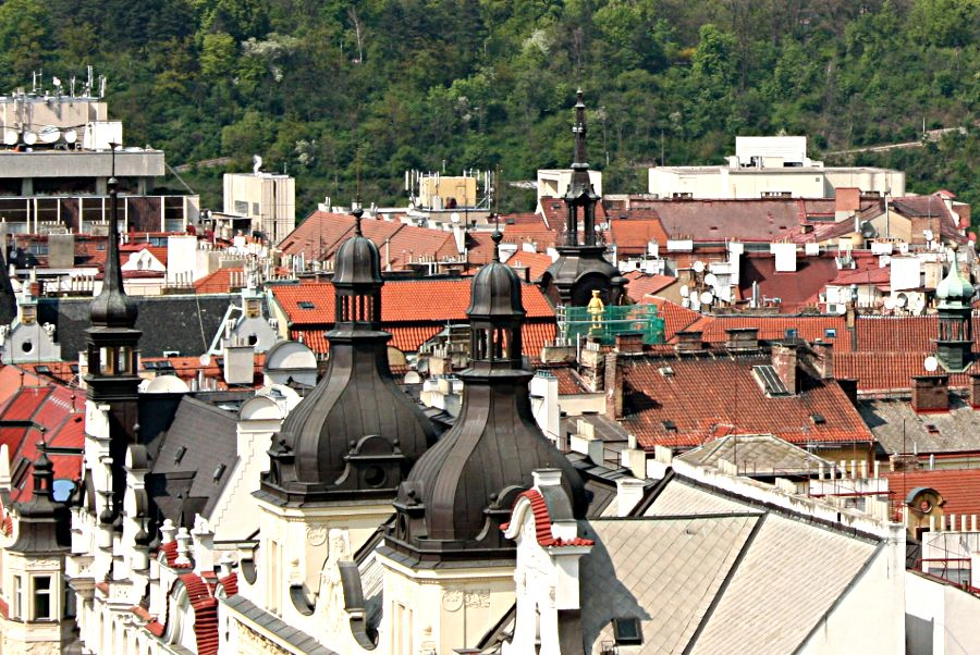 Black spires and red rooftops with white chimneys and satellite dishes