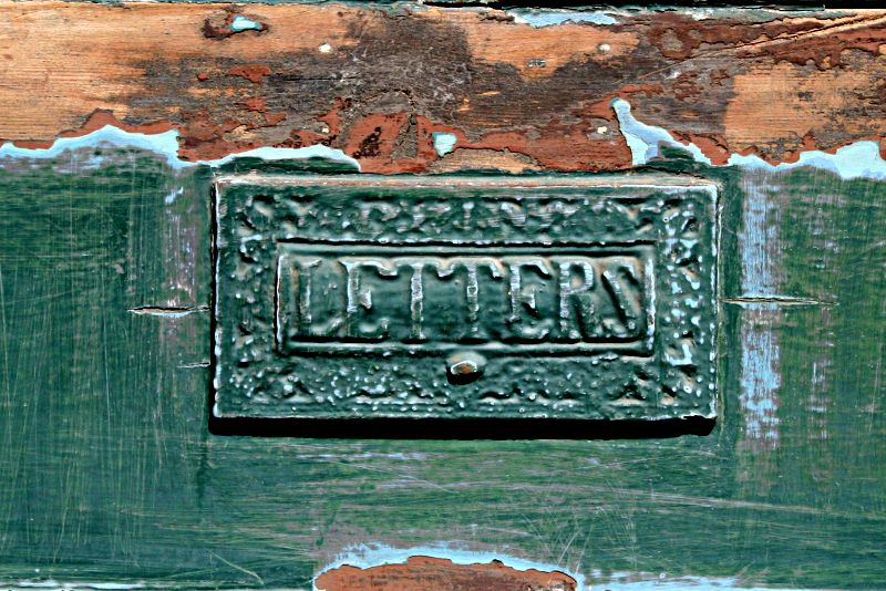letter box in partly painted green door
