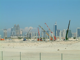 Constructing the Dubai Humanitarian City with Dubai's Sheikh Zayed skyline in the background - click for full size view