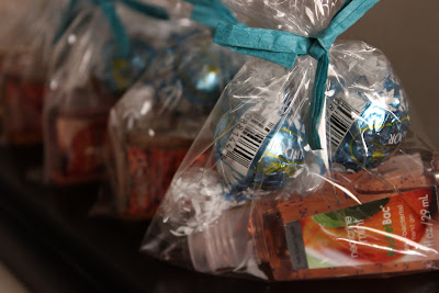 This is a picture of the baby shower party favors. They are small bags filled with lindt candy balls, a travel size bath and body works hand sanitizer and are tied with blue yarn.