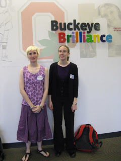 A photo of Noranne and Melanie standing in front of a sign that says Buckeye Brilliance