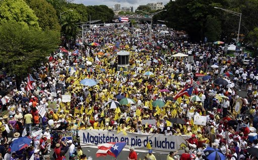 Demonstrators, holding a banner that reads in Spanish 'Teachers union at the battle front,' march in San Juan, Thursday, Oct. 15, 2009