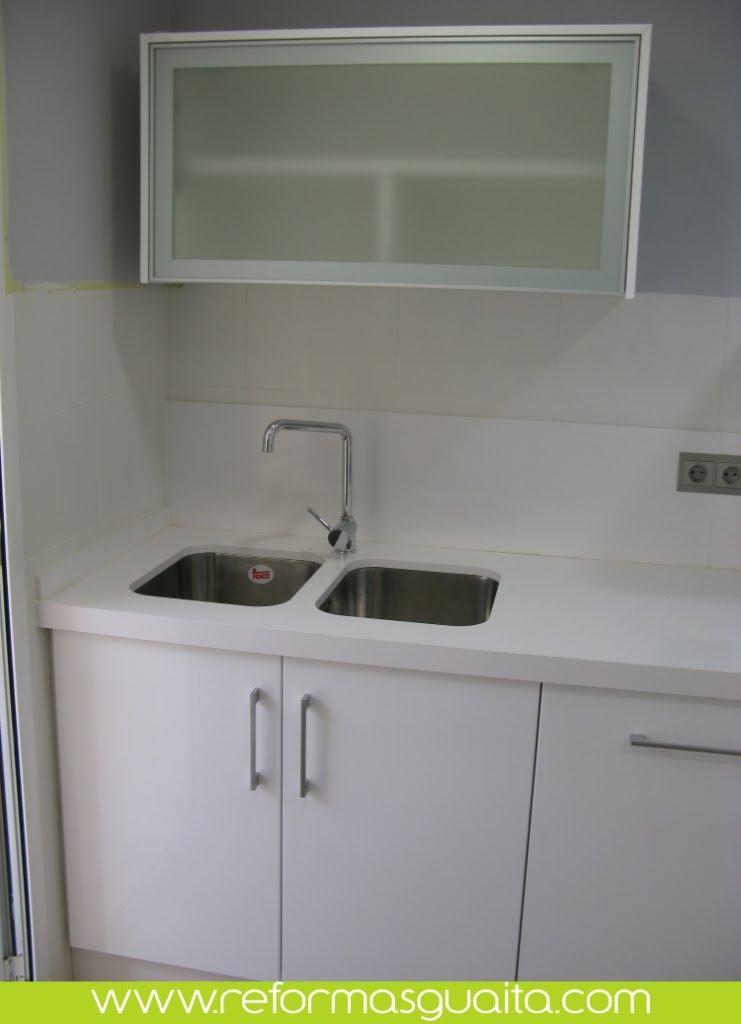 las paredes de esta cocina han sido revestidas con un azulejo blanco mate colocado hasta la altura de la campana