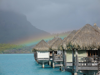 Rainbow over huts over the ocean