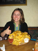 Woman gives thumbs-up to a large plate of nachos