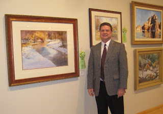 Artist Roland Lee poses with painting of Icy River at Sears Art Show