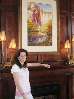 Elizabeth Bingham in the library of her home with Roland Lee painting of Zion National Park