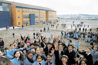 fotografía de un grupo de estudiantes, en el fondo se ve el edificio de un establecimiento escolar