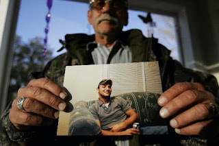 Guy Fulcher holds a photo of his son Brian Sessoms.