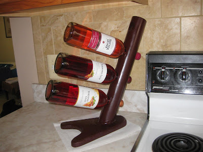 simple homemade wine rack, PVC pipe, wood, wine bottles