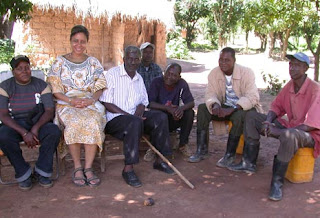 Rory Anderson with village elders and others in the shade of a mango tree.