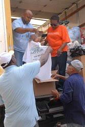 Rev. Randy Vaughn, left foreground, of Mount Sinai Missionary Baptist Church and volunteers from the church unload supplies from delivered by World Vision.