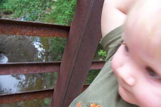 toddler on bridge over creek