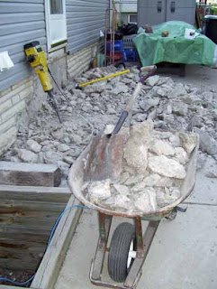 Rubble from the back steps in the process of being cleared.