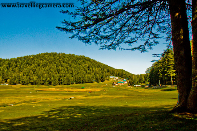 Khajjiar Trip during my Sabbatical - Part 2 : Posted by Vibha Malhotra at www.travellingcamera.com : During my Sabbatical in Feb this year, I went for a solo trip to Dalhousie, Himachal Pradesh on a friend's recommendation. While staying in Delhi, I took a taxi to Khajjiar and reached there early morning, which  was a good thing. The place is a very popular tourist spot and is therefore almost always crowded. In my case, early arrival ensured a stress-free stroll and some amazing pictures.The ground was covered with soft grass and the area was lined with tall deodars lending it an appearance of a bowl. Tourists had only just started arriving. Therefore, there were only a few cars parked. The lake in the center could have been better maintained though.Houses with colorful sloped roofs dotted the scene here and there adding more character to the scene. A close-up of some of the buildings in the area. houses with sloped roofs fascinate me a lot.One of the old houses in a typical