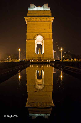 A Late Evening Glance at India Gate with my Travelling Camera: Posted by VJ SHARAM at www.travellingcamera.com : The India Gate is one of the largest war memorials in India. Situated in the heart of New Delhi, India Gate was designed by Sir Edwin Lutyens. It is a prominent landmark in Delhi and commemorates the members of the erstwhile British Indian Army who lost their lives fighting for the Indian Empire in World War I and the Afghan Wars. Originally, a Statue of King George V had stood under the now-vacant canopy in front of the India Gate, and was removed to Coronation Park with other statues. Following India's independence, India Gate became the site of the Indian Army's Tomb of the Unknown Soldier, known as the Amar Jawan Jyoti.(Courtesy: wikipedia)Standing Tall against the SkyIndia Gate looks amazing in the evening with well placed lights around it... Many Families in Delhi comes to India Gate in the evening and some of them come with all the stuff for dinner... There are luh green lawns around India Gate where one can sit and enjoy with family and friends...Lonely and Majestic..All these photographs have been shot without Tripod so they are blurry, which is more clear in the photograph above... Once I had seen an exhibition by Anindo Ghosh @ IHC Delhi and he had some brilliant shots of India gate, serial lights around it and their reflection in water ponds on its sides... All of them were stunning shots of INDIA GATE...A Permanent Flame...I usually visit India Gate with friends in the evening and take our Dinner at Andhra Bhavan which is on the circular road around India Gate... we need to take the car on Ashoka Road and then a cut... Food at Andhra Bhavan is good and they serve Thali @ 80 Rs for one person.. Its Veg Thali with unlimited service of Rice, Roti, Number of dishes... Few things like Curd, Papad, sweet-dish is served only once... Non-Veg is available but we didn't like it.. So wehenever we go to Andhra Bhavan for Dinner, we only take Veg Thalis... In Lunch time Puri is served instead of Rotis...Secure 24 * 7..Security of INDIA GATE is taken care by Army and there is some restricted area near to actual Gate where nobody can go... There is circular iron-chain around main gate which defines the boundary for normal civilians... and Security people look great in their unique attire with nice boots and powerful guns...Every Night Hundreds Celebrate their Indian Origin...Normally people visit the pace but hit season is summers and monsoons... Of-course, one can find huge crowd at INDIA GATE everytime but yes evenings are more crowded... In the evenings, there are lot many eating options around it which starts from Chana-Jor-Garam, Bhel-Puri, various brands of Ice-Creams with different options, Pani-Puri, Chats and what not... Reaching out for the Sky... An Image of India... Day shots of India Gate from moving Car when we were heading towards India Gate from Rashtrapati Bhavan..Names Engraved in the Heart of India...A Moment to Reflect....The More I See the World, the Closer I Feel to India....