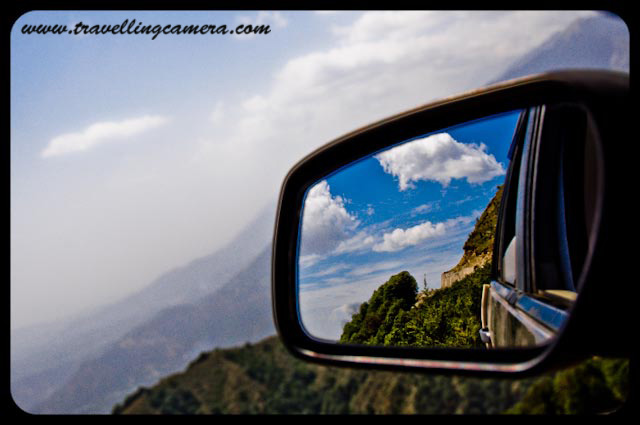 Travelling-Camera sharing some high altitude captures from Road Journey to Bir-Billing: World Famous place for Paragliding: Posted by VJ on www.travellingcamera.com : VJ capturing reflection of beautiful Billing on car-window... Travelling Camera @ Billing, World's famous Para-gliding site...After a long road journey through Mandi, Hamirpur, Sujanpur-Tira, Palampur, Dharmshala and Baijnath, we finally reached Billing, world famous site for Paragliding.Just crossed Bir to reach Billing for experiencing paragliding on world's famous site in Dhauladhar Mountain range... Under legs of mountains and surrounded by tea gardens Bir a small village with a Tibetan Colony and monasteries in Kangra district of Himachal Pradesh(INDIA) which serves as a landing ground and a base for Hang/Para-gliders. Launching or take-off place is BILLING which is a little meadow at 2408 meters (8550 feets) on the Dhauladhar ranges: 14 kilometers up from Bir. This meadow is one of the wonders of nature seems like perfectly designed as a launch pad. Billing has become a legend on the international paragliding circuits and a destination for World Champion Paraglider pilots. The meadow directly above the villages of Bir and Chaugan is one of the best gliding sites in the world...Travelling Camera trying to capture wonderful colors of BILLING through side mirror of Hundai i10 ... From Billing the mountain range runs all the way to Dharamsala by separating the Kangra district distrc from Chamba. To the north of the meadow is the high peaks and to the south the plains. The fall from the meadow is about one kilometre and an average straight top to bottom flight to the Chaughan landing area lasts for about 30-45 minutes.A View of Jogindernagar region from a small road towards BILLING from Aehju...Road between Aehju and Bir is fine but the stretch of 10 kilometers was in very bad conditions. Its a very narrow road and rough at most places... Careful driving is very important because there are deep valleys on the other edge of this road... Initially its discouraging but after reaching BILLING, we found it worth it... A View of landing place BIR from the most famous paragliding destination in Dhauladhar range... The huge Dhauladar mountain range and Kangra valley with its panoramic views offer opportunities for high altitude flying for more than 190 kilometers. The Dhauladar range runs from Dalhousie in the North West of Himachal Pradesh in a curving arc of south-east to Mandi. Billing lies roughly midway between Dharamsala and Mandi and to the south west of Manali/Kullu valley.Tourist Vehicles @ BILLING, amazing para-gliding site in INDIA.. Billing is very well known in world for having the distinction of organizing the very first Paragliding competition according to the rules of Federation Aeronautique International. The Department of Tourism of Himachal Pradesh also organizes 'Para Gliding Pre world Cup' at Billing- Bir . It is also the place for Hang gliding and Para Sailing...Travelling Camera capturing the only house at high altitude of Billing Hills in Dhauladhar Range...