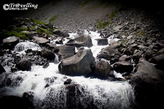 Waterfalls on the way to Mani Mahesh Lake : Posted by Vishal Sharma on www.travellingcamera.com : A long trek through Pir Panjal mountain range of Himalyas : PART-1 :  Himachal Pradesh is home to many historical and religious sites.... and also known as State of GODs... The state boasts of several exciting pilgrimage trails leading to sacred temples... The Manimahesh Yatra is one such pilgrimage which starts from Lakshmi Narayan Temple in Chamba and ends at the Manimahesh Lake  in Bundhil valley... Here are some PHOTOGRAPHS of Waterfalls on the way to Manimahesh : MANIMAHESH YATRA 2010There are countless number of waterfalls on the way and water in all of the streams in considered very medicinal... I met a gentleman who told that some medicinal plants of Himalayas are found in this region and water is very good for skin, breathing and other things which I forgot :)The Manimahesh Lake is believed to be one of the abode of Lord Shiva as per the Hindu mythologies... Notice pilgrims in colorful dresses in this photograph and try to think about the height of this waterfall... Last time I had such huge waterfalls on Shrikhand Trek ...The pilgrims walk along the rocky path completely bare footed, singing Bhajans and praying ecstatically to Lord Shiva... After reaching Mani-Mahesh Lake they take dips in the holy water. With the termination of the Manimahesh Yatra, the devotees visit the ancient temple of Chatrari, which is located between Bharmaur and Chamba...Some of us tried to climb up these hills on with these water streams but its near to impossible to complete with these streams...The wonderful route not only attract the pilgrims but also excites the adventure lovers and tourists...Freshness flowing through heavy rocks @ Manimahesh, Chamba, Himachal Pradesh, INDIAWalking to the way of the Manimahesh Lake is a wonderful experience... One will forget the pains of the tiresome journey watching the wonderful natural scenery and fresh environment around.... However one sho