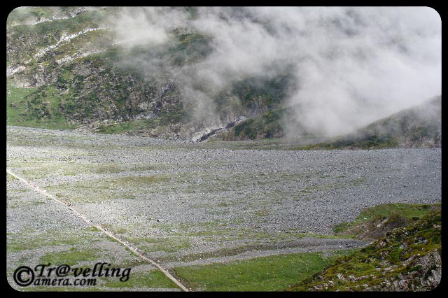 Typical Trekking routes on the way to Manimahesh Yatra in Himlayas (Pir Panjal Mountain ranges) : Part-1 : Posted by VJ Sharma @ www.travellingcamera.com : For last few day I have been sharing some of the photographs clicked during my Trekking experiences to Manimahesh in Chamba Distrcit of Himachal Pradesh... Today I thought of sharing some photographs of this trek and how these treks crwal on Himalayan Hills...So here are some pf the photographs showing typical trekking routes to Manimahesh...Its a wonderful trekking opportunity on Pir Pajal hills of Himalayas... As you can see in these photographs, these tracks look very small against the huge hills... and these are just the tips of the whole mountain range which is difficult to capture in one shot... Notice the small track on right bottom of this photograph and shaodws due to hill top... I am sure you would be able to imagine the height of this hill against sky and feel the mment when someone is moving on this trek... If you able to do so, expect some clouds coming on your way in few seconds :-)Here is same photograph with some marks around the main trekking path to Manimahesh... If you had some difficulties understanding the first photograph, now it should be easy to enter the virtual world of himalyan Treks :-)If you are able to imagine yourself on this route, I am sure you would be able to relate to this photograph... Now we have reached a height after different curved paths.... Here is a view of a valley with some plain area which is being used for taking rest in the rested tents there... First photograph was clicked between this point and the tent-area we are seeing here....Again some marks to help you better understand the route... route starts from left most mark.. breaks at right-top end of this photograph... and after a hidden route (covered in first photograph...) , path again move towards the left...Hold on... See this photograph and imagine yourself standing somewhere on this path... can you guess how long in this stretch? It would be nice to hear back from your about it through comments in this post... It was a very long trek between two huge moutains... imagine that bottom of this hill looks like a plain valley and try to have a view of this hill in your mind.. Believe me, it was an amazing experience... and I fully enjoyed it...Here is same photograpg with some marks around trekking path between two huge hills on the way to manimahesh in Chamba District of Himachal Pradesh... With this I going to stop here and would share more trekking experiences through hills covered with snow and clouds....
