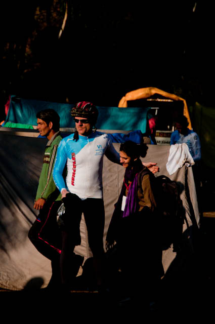 MTB Riders getting ready for second day Hiking and Biking : Posted by VJ SHARMA on www.travellingcamera.com : Hope you have already check other posts on MTB Himachal 2010 which talks about flag-off from Ridge ground, Rides during first day and some glimpses of this event... Today I am going to share some of the photographs of first morning(after camping) of this event... So here are few photographs of second day morning with some details about the activities around the camp side...Although there was sunlight but it was too cold in the morning... Many of us were hesitating to have bath there but finally we got motivated after seeing hot water on other corner of the camping ground... I think you can make a guess that why people are standing behind these tents and nobody in the front... Coz everyone is looking for sunlight and no one can't afford to stand in shadows :-)Mr. Dutta from Maharashtra assisting other rider in repairing the bike... Dutta ji, a passionate biker from Maharashtra who were bare feet throughout the journey... And you can also see that he is half T-Shirt... He is not worried about winters as he always lives like that irrespective of the season... A very humble and calm guy... Nice to meet you Dutta Ji !!!There were few folks who were leaving on second day... This includes some of the riders and few photographers... So everyone was saying bye to each other by getting appropriate details to be in touch... Here Runjhun (PHOTOQUEST participant) meeting Peter to say 'Good-Bye' and 'All the Best !'Due to rough and muddy roads, all the riders needed to take proper care of their bikes.... everyone used to clean and repair their cycles everyday... I was amazed to see people repairing their bikes with ease... They used to disassemble their bikes and re-assemble again after cleaning and repairing... Many times they used to talk about various types of bikes, companies, gears and other accessories... although I was not able to relate to most of the stuff... The only thing I noticed was that Military people and Nepali gang had best bikes in the camp...Folks are ready and just waiting for the final call from Marshals... Some of the riders are just warming up for the rides... On second day they had to ride till one point (?? KM) and then they had to cross a river to hike a mountain with their bikes.. This whole stretch of hiking was 12 Kilometers... It was very tiring... We were four  PHOTOQUEST participants who were together during this hiking session and all of us were down during the half way... Everyone was hungry and we were not carrying anything with us... On the way we asked for water at a local village an they gave us apples as well :-) ... Those Apples were amazing and now we had some energy to continue...  For rest of the story, I will share another post with Hike and Bike Photographs...Here is a photograph of Shainj School where we stayed during first night of MTB Himachal 2010... Lovely place under blue sky and surrounded by hills... Nothing like it !!!Here comes all the riders ready for various challenges of the day... The man in the front was a retired policeman and was there in MTB for first two days... When I asked