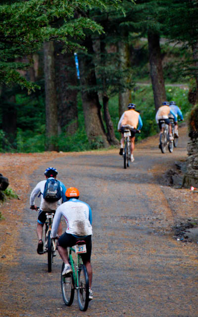 aFirst Day rides during MTB Himachal 2010 - A Road journey in Himalayas : Posted by VJ SHARMA on www.travellingcamera.com : Hope you have already checked flag-off and some glimpses of MTB Himachal 2010... If not, I would recommend you to check out following two links before checking these photographs of very first day...Here are few more photographs of first day of MTB Himachal 2010 - Shimla  Mashobara Shainj (Final Destination for the day)MTB Riders climbing a normal height on good roads on first day...The flagoff from Shimla Ridge was a great improvement over previous year's start from the Peterhoff hotel grounds - more accessible to the general public and the first day's stages were a bit of a warm up... All the riders started from Ridge and moved towards Mashobara.. A few kilometers from Mashobara, first stretch for racing had to start... All set and it started in batches for 8-12 riders...Some of the MTB riders were very fast and they always lead the whole group... A Group from Nepal and another was Indian Army group... They had best cycles as compared to other folks..One of the rider coming towards the bike after taking rest.. It was raining, so some of us stopped riding and rested till it stopped... Notice the road conditions and imagine how they would have been after rains...As far as I remember, there were only two girls who were riding.. One was indian and other was from Nepal... Here is Number 57, Indian Rider who had great sense of humor :-)Another rider of the gang who faced lot of hurdles on the way... But he rode till the end...Every rider had a diary with him/her.. Before starting of any stretch, volunteers used to write down the time in those diaries and duration was calculated on ending of each stretch... Riders used to move in various groups and final timing had to be calculated on last day...Can you guess who are these?Here comes Mr.Rocky with his racing car... For now I am not explaining anything about it because I will have a separate post on this vehicle :-)It had been raining the day before and was still overcast ... After covering few kilometers, it started raining and since we were in Forests of Deodars, there was no place to hide from rains....Here comes Mr Suban Walia, who joined the gang mid-way... I think, he had just parked his Swift to take some photographs of riders on the way.... A true fan of NIKON We met many friends during this event and one of the Photographer called all the dogs with same name