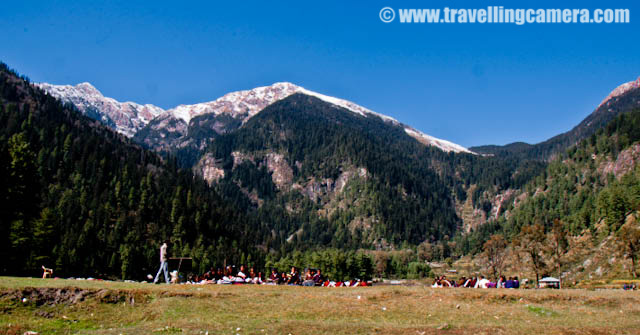 One complete day well spent at Kullu Sarahan - 4th day of MTB Himachal 2010-01.jpg: Posted by VJ SHARMA on www.travellingcamera.com : During MTB Himachal 2010, there was only one rest day for riders and they had chosen most amazing place for having rest... although no one wanted to rest inside the camp.. Most of the riders thought of exploring the natural beauty of the places around Sarahan Villlage... Here are some of the photographs showing the whole fun we had during the fourth day of MTB Himachal....A view of Sarahan Village in the middle of snow covered mountains... The village has a huge ground near Government school...Three shining trees on the other end of the village... There are few shops around these trees and people have some guest houses for visitor.. Its a beautiful village, but there is no decent hotel or guest house... But there is a HPPWD guest house on the top of a hills on the side of the ground you see in first photograph...Some houses around the main ground in Sarahan village...There were some water streams flowing around this ground and they had chilled water.... melted snow from the surrounding peaks...School Children enjoying their studies in the open... Imagine how much exciting it would be to have a class in a huge green ground surrounded by snow covered peaks... and water streams flowing on both sides of your class area....There was a small dairy in the village and the milk is delivered to the nearest town and it was most difficult task to deliver it on time everyday... No transport and one has to go 12 kilometers down to reach the place and come back....Another photograph of Open School in Sarahan Village of Kullu Distrcit in Himachal Pradesh... Masti ki pathshala...Its evening now and time is to go back to our camps for bonfire, snacks and booze....A typical roof of a Himachali House... This roof is made up of slates created from a very hard/shining stone... First a wooden framework is created and these slates are installed on top of tha
