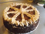 De taart af en bespoten en gegarneerd met cacaopoeder.
