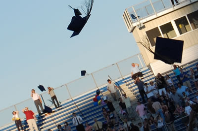 Graduation caps tossed into the air.