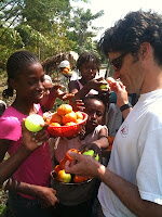 A volunteer and local Haitians looking down at several bowls of fruit.