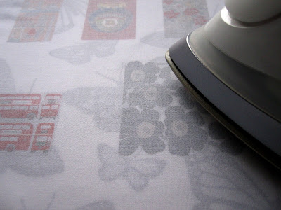 Iron pressing the wrong side of a piece of printed fabric.