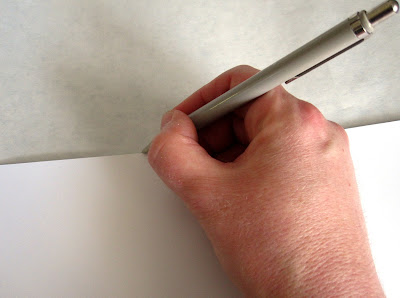 Drawing a line along the edge of a piece of cardboard onto a length of paper.