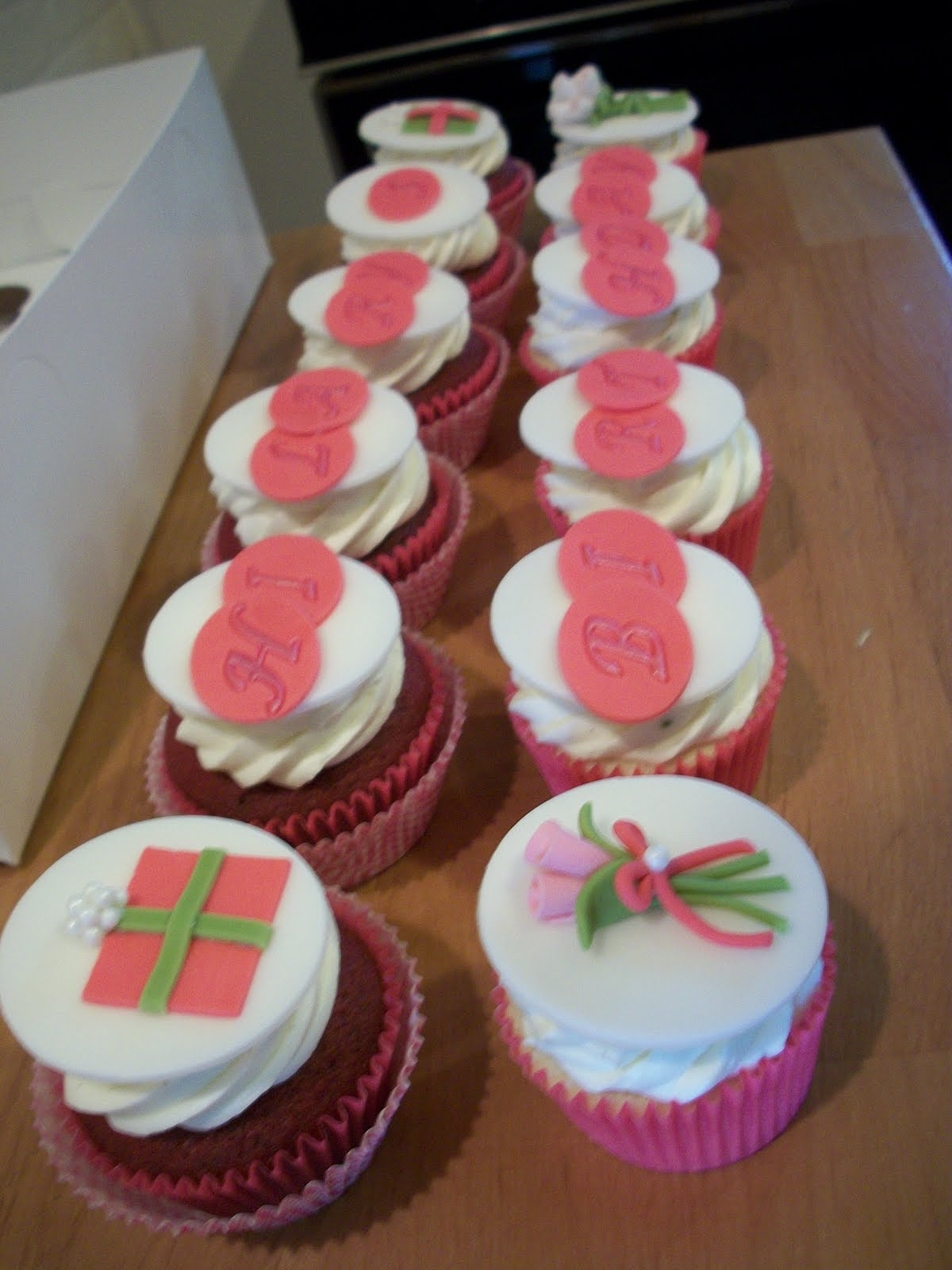 Script letters, gift boxes and flower bouquets all of fondant