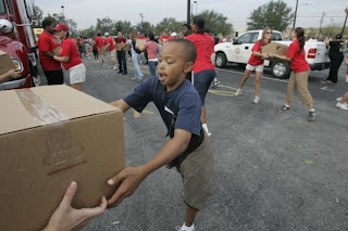 Gerald Barnett, 10, takes a box in a human chain of volunteers preparing to handout boxes of food to Houston residents