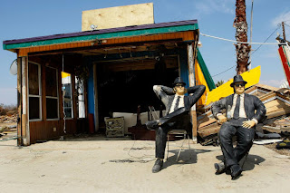 Sculptures of the Blues Brothers sit in chairs in front of a demolished business on HWY 87, September 18, in Crystal Beach